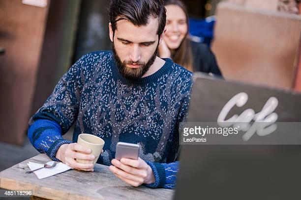 Homme barbu boire un café dans un café avec terrasse