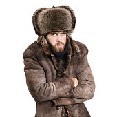 Young bearded man in the coat and earflaps hat, feel cold, isolated on a white background