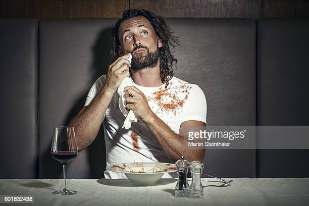 Bearded man finishes dinner and blotted his white shirt