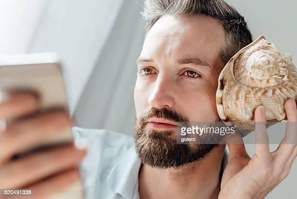 Bärtiger Mann hält Smartphone und Schale am Ohr hören