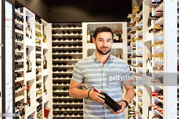Bearded man holding wine bottle in a liquor store