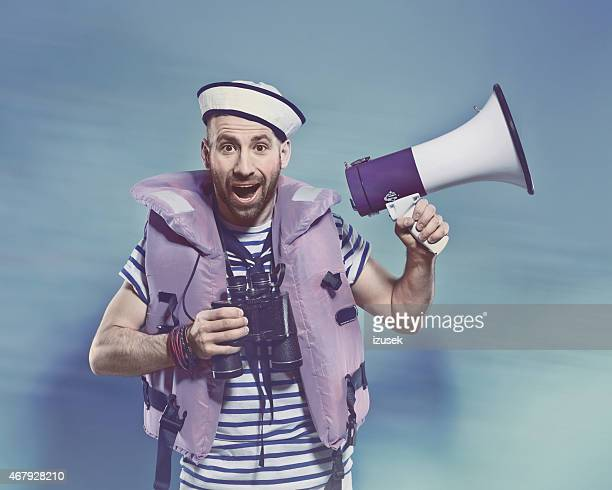 Bearded man in sailor style outfit holding binoculars and megaphone