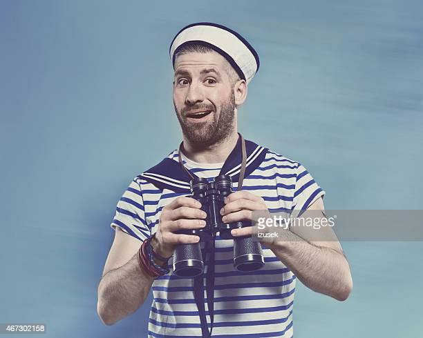 Bearded man in sailor style outfit holding binoculars