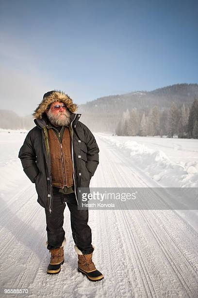 Bearded man in winter jacket in snow.