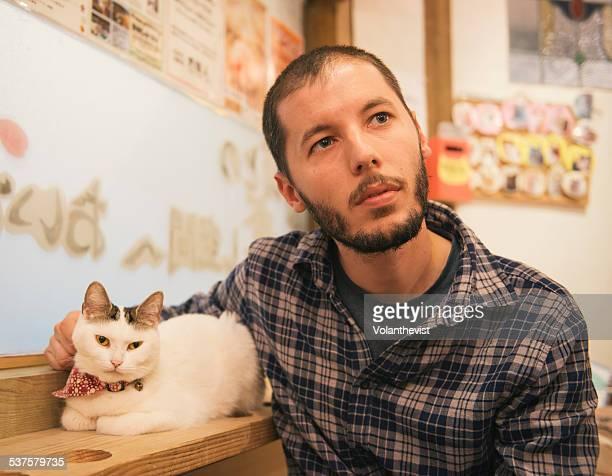 Bearded man petting a white cat