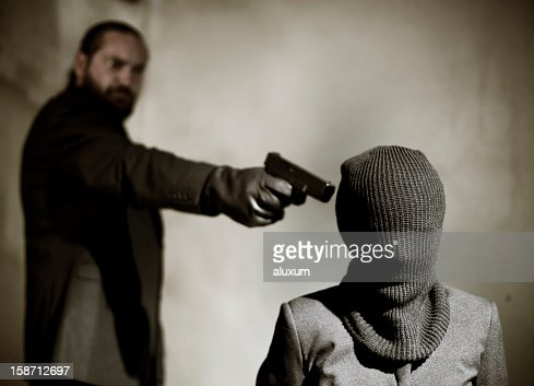 Bearded man pointing a gun at a man's temple to execute him