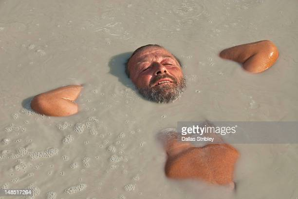 Bearded man relaxing in therapeutic volcanic thermal mud pool, Levante Beach.