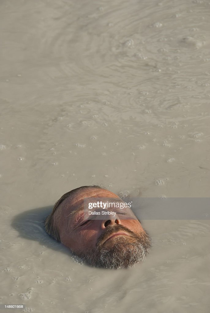Bearded man relaxing in therapeutic volcanic thermal mud pool, Levante Beach. : Stock Photo