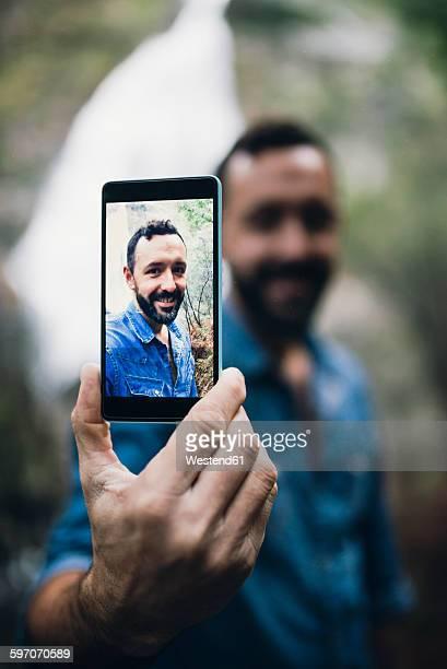 Bearded man showing selfie on display of his smartphone