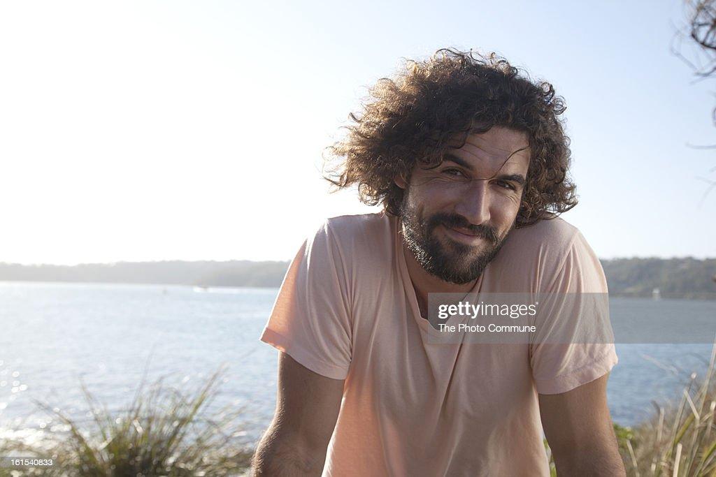 Bearded man sitting near ocean smiling : Stock Photo