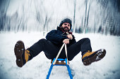 Bearded man sledding on a beautiful winter day
