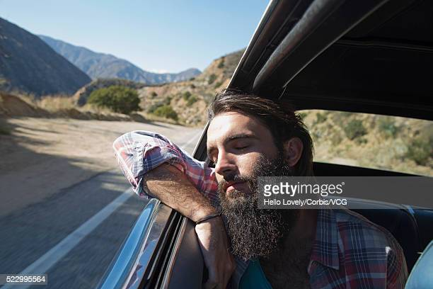 Bearded man sleeping in car