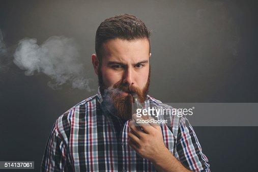 Bearded man smoking wooden pipe