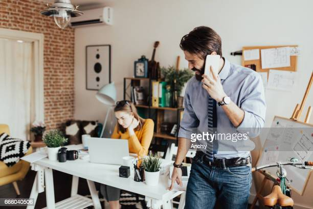 Bearded man talking on the phone while cute girl is using laptop