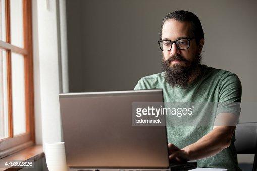 Bearded Man Using Laptop By Window