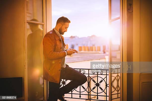 Homme barbu à l'aide de smartphone en avant de la fenêtre
