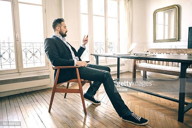 bearded man using smartphone in homeoffice