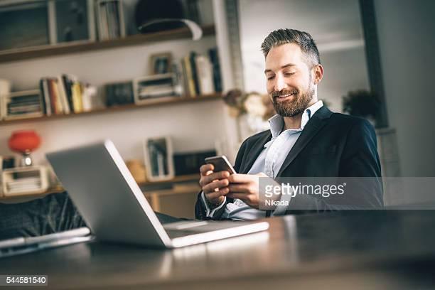 Homme barbu à l'aide de smartphone dans le bureau