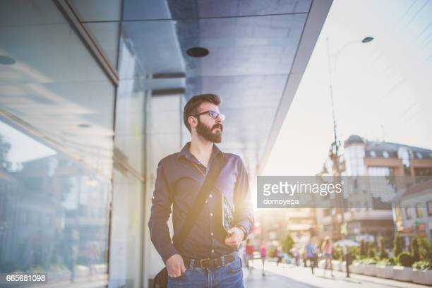 Bearded man walking down the street and holding digital tablet