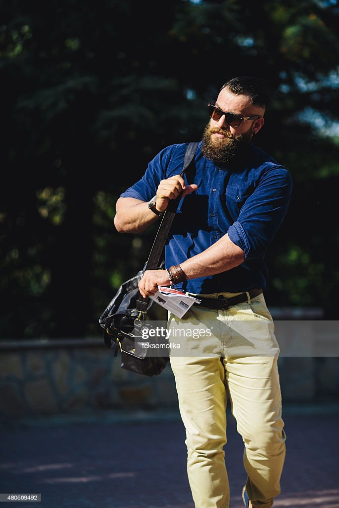 bearded man walks through the city : Stock Photo