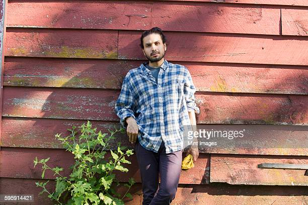 Bearded man wearing a checkered shirt leaning against a wooden wall in the shade.