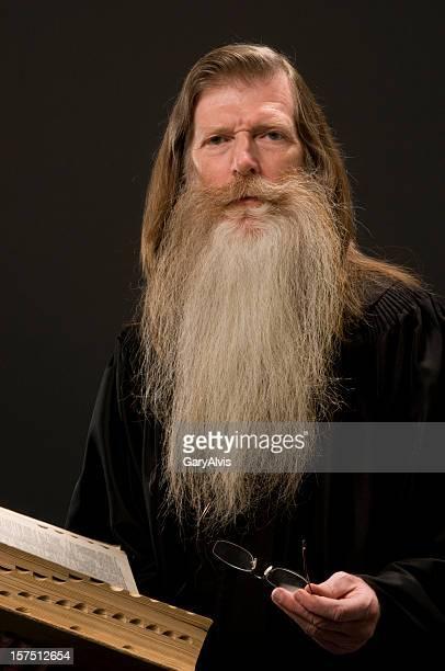 Bärtiger Mann trägt scholar's Bademantel hält Buch/Bibel-Blick in die Kamera