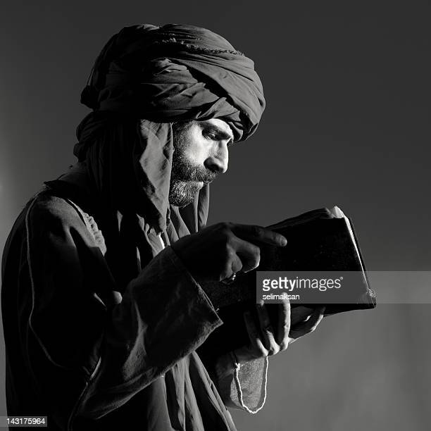 Bearded man with headscarf reading old antique book