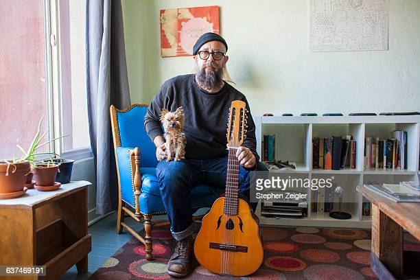 Bearded man with small dog and mandolin