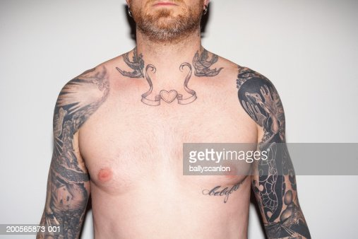 Bearded man with tattooed arms and neck, against white background : Stock Photo
