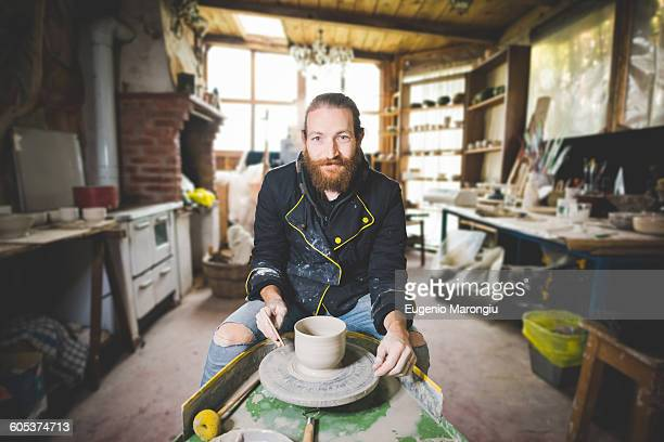 Bearded mid adult man in workshop sitting at pottery wheel making clay pot, looking at camera smiling