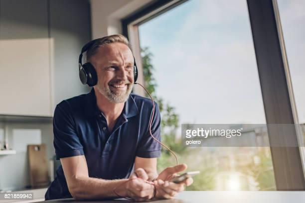 bearded midaged man enjoying listening music at table indoors