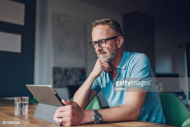bearded midaged man with glasses at table with tablet