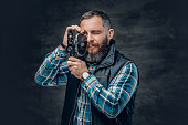 Portrait of bearded middle age male holds vintage 8 mm video camera over grey background.