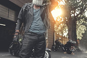 Mature biker is standing near motorcycle and holding helmet. He wearing clothes made of leather. Low angle. Copy space