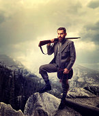 Bearded hunter man in old-fashioned hunting clothing with antique gun, rocky mountains and cloudy sky on background. Hunt lifestyle