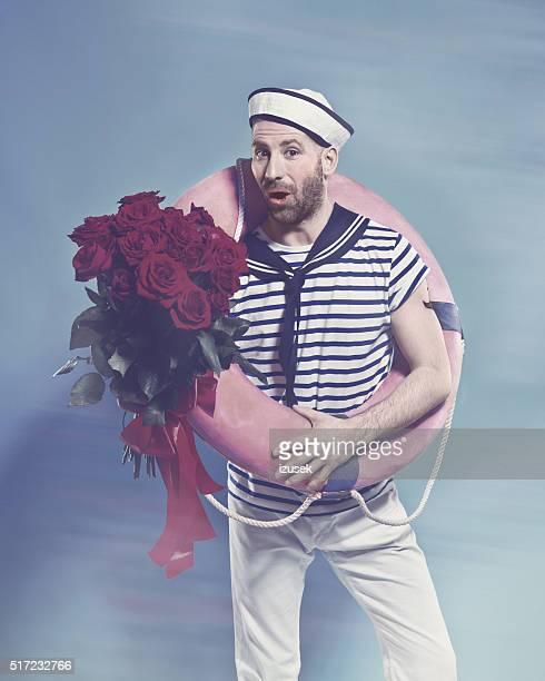 Marin barbu tenant bouée de sauvetage et bouquet de roses