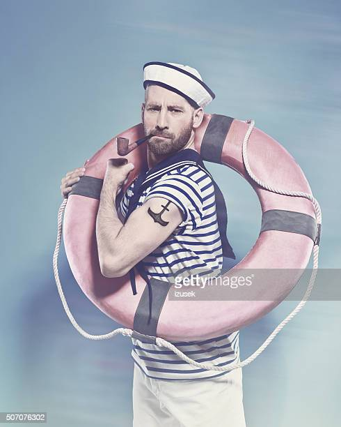 Bearded sailor holding lifebuoy and smoking pipe