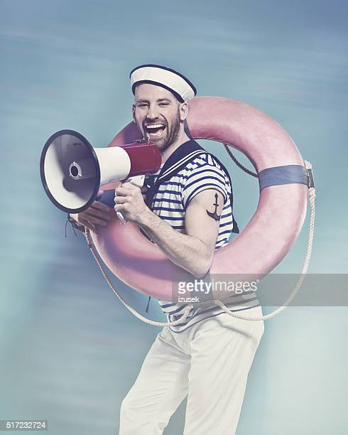 Bearded sailor holding lifebuoy, shouting into megaphone