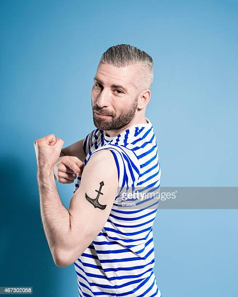 Bearded sailor man showing his anchor tatoo
