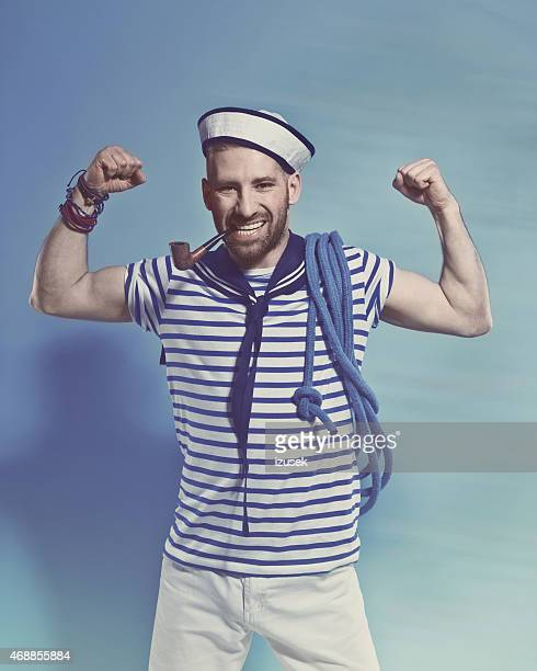 Bearded sailor man smoking pipe and flexing his arms