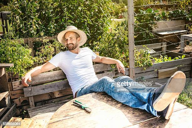 bearded smiling man relaxing with feet on table in garden