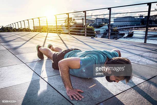 bearded sportsman  man  doing arm push-ups in berlin city