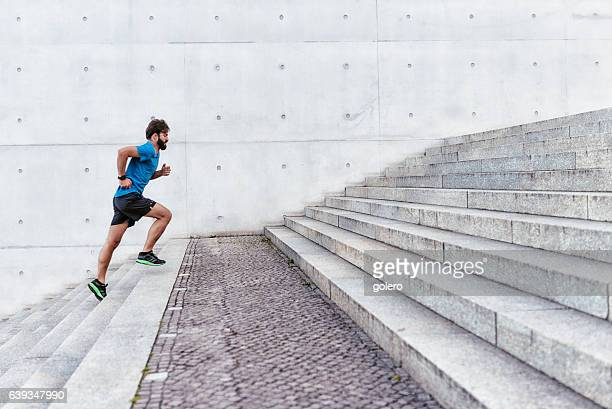 bearded sportsman running up outdoor stairway