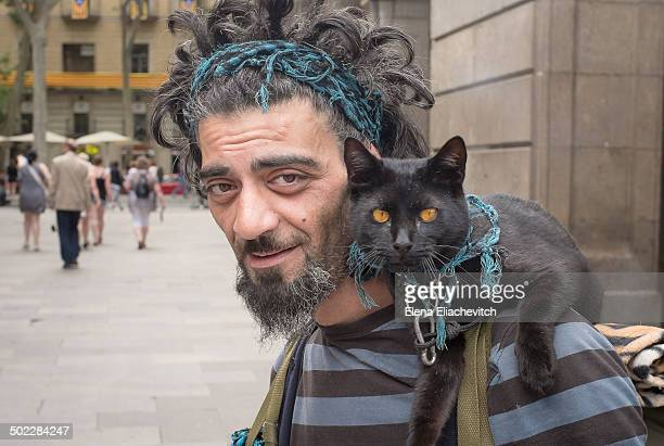 Bearded stranger with black cat on his shoulder on a street in Barcelona