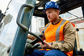 Confident bearded worker wearing protective helmet and reflective vest driving lift truck while working in port warehouse, portrait shot