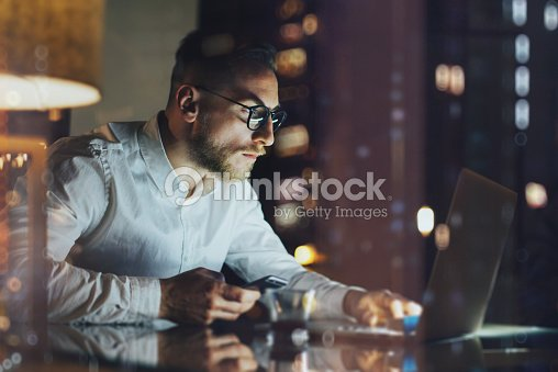 Bearded young businessman working on modern loft office at night : Stock Photo