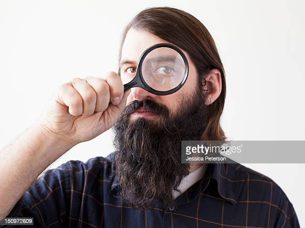 Bearded young man looking through magnifying glass