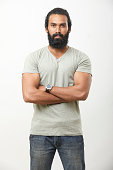 Bearded young man posing with crossed arms on white.