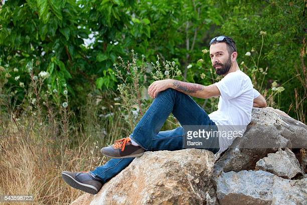 Bearded young man sitting on the rock enjoying the view