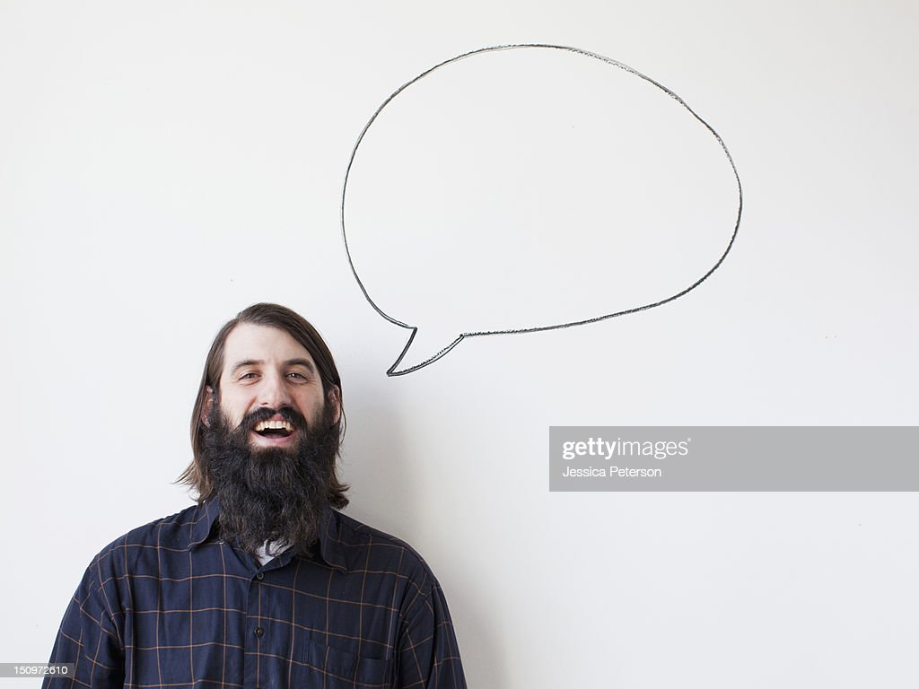 Bearded young man standing next to speech bubble on white background